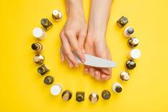 Концепция искусства ногтя Женщина делает маникюр на таблице Гель полирует на маникюре и женских руках на желтой предпосылке стоковое изображение rf