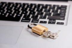 Концепция компьютерной безопасности и защиты данных Компьтер-книжка с запертым замком и ключ на ем стоковая фотография
