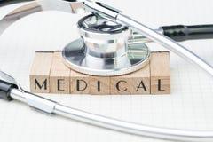 Концепция медицинских или здравоохранения образования, стетоскоп металла положенный на деревянные печати с алфавитом строя слово  стоковые изображения rf