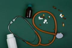 Концепция медицины - стетоскоп, красочные таблетки и медицинские бутылки на предпосылке зеленой книги стоковая фотография