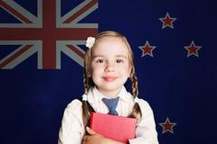 Концепция Новой Зеландии со студентом девушки ребенка с книгой против предпосылки флага Новой Зеландии стоковые изображения