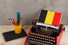 Концепция политических, новостей и образования - красная машинка, флаг Бельгии, тетрадь и канцелярские принадлежности стоковые фото