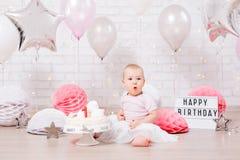 Концепция дня рождения - изумленная маленькая девочка с тортом над предпосылкой кирпичной стены со светами и воздушными шарами стоковое фото rf
