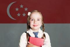 Концепция Сингапура со счастливой девушкой ребенка в школьной форме с книгой против республики предпосылки флага Сингапура стоковая фотография rf