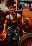 Концепция человека Красивые остатки empoyee человека на кабине трактора Уверенно работник человека на затяжелителе backhoe Сильны стоковое изображение