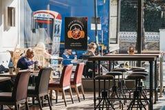 Кофе женщины выпивая и чтение в Pret кормушки, Лондона, Великобритании стоковые фото