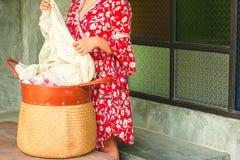 Корзина нося ткани прачечной азиатской женщины стоковые изображения rf