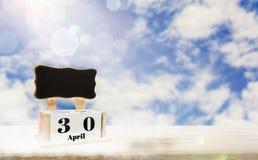 Коробка календаря с классн классным для входя в текста, дней 30-ое апреля устанавливает на деревянном столе, яркой предпосылке го бесплатная иллюстрация