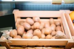 Коробка со свежим кивиом на стойке в продовольственном магазине, никто стоковая фотография