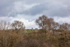 Ландшафт с силуэтом стоящего счастливого человека, поднятыми-вверх оружиями на горе стоковая фотография
