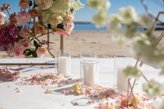 Лепестки свежего цветка лежат на поле рядом с украшенным сводом свадьбы и белыми свечами Украшение события со свежими цветками стоковое изображение rf