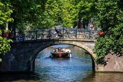 Летний день в Амстердаме с плаванием шлюпки на канале стоковая фотография