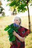 80 - летняя женщина с букетом цветков в ее руках стоковое изображение