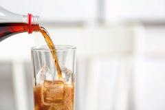 Лить кола от бутылки в стекло на запачканной предпосылке, крупном плане стоковая фотография rf