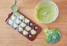 Лить помятое детское питание в контейнер на деревянной доске для замерзать стоковое фото