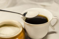 Лить сахар в чашке кофе стоковые фотографии rf