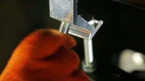 Лихтер в работая перчатках затягивает винт струбцины видеоматериал