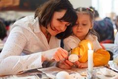 Львов, УКРАИНА - 11-ое марта 2018 Мама и дочь красят пасхальные яйца на таблице стоковое изображение