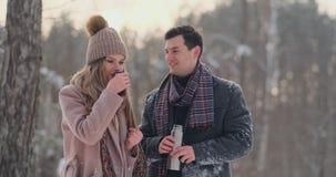 Любящие человек и женщина пар в чае леса зимы выпивая от thermos Стильные человек и женщина в пальто в акции видеоматериалы
