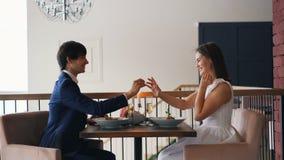 Любя молодой человек делает предложение руки и сердца к счастливой девушке на дате в ресторане сидя на таблице и давая ей кольцо видеоматериал