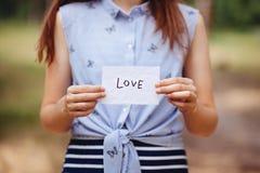 Любовь - женщина и карта со словом, днем Святого Валентина или концепцией вероисповедания стоковые фотографии rf