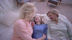 Любовь семьи, счастливая мать с дочерьми совместно имеет время и падение потехи на кровать сток-видео