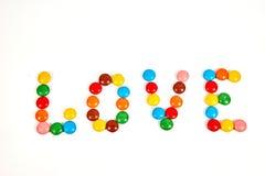любовь слова от красочной конфеты изолированной на белизне стоковая фотография rf