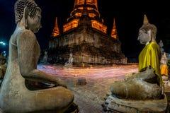 Люди буддистов идя с освещенными свечами в руке вокруг древнего храма стоковое фото