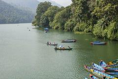 Люди в пестротканых деревянных шлюпках на озере против фона зеленых джунглей стоковое изображение rf