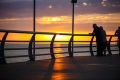 Люди идут вдоль прогулки в желтых и оранжевых лучах солнца на заходе солнца стоковые фото