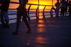 Люди идут вдоль прогулки в желтых и оранжевых лучах солнца на заходе солнца стоковое фото