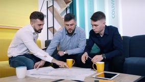 Люди коллег работая с чертежи и планы в офисе, правильные неточности используя планшеты сток-видео