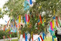Люди путешественников присоединиться и пишущ желания на бумаге и вид на бамбуковом дереве в фестивале Tanabata или звезды японско стоковое изображение rf