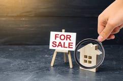 Лупа смотрит деревянную стойку дома со знаком для продажи Продажа дома или квартиры и свойства housing стоковое фото
