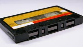 Магнитофонная кассета вращает на белой предпосылке акции видеоматериалы
