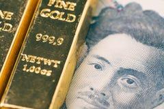 Макрос снятый сияющего бара золота слитка миллиарда на японской банкноте использующ как вклад или сбережения богатства в финансов стоковое фото