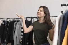 Маленькая девочка, брюнет, в магазине одежды, усмехаясь стоковое фото