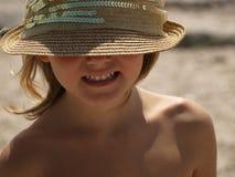 Маленькая девочка в бежевой шляпе солнца с улыбкой стоковые фото