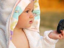 Маленькая девочка в белом пальто с крышкой объектива в руке стоковые фото