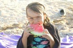 Маленькая девочка ест кусок арбуза летом на пляже стоковое изображение rf