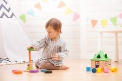 Маленькая девочка играет с пирамидой игрушки дома стоковая фотография rf