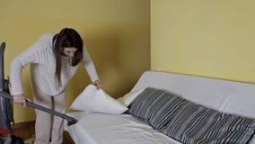 Маленькая девочка использует пылесос для того чтобы очистить пыль в подушке сток-видео