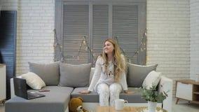 Маленькая девочка лежит на софе, сидит на софе и получает вверх от софы С хорошим настроением и красивой улыбкой смотрит сток-видео