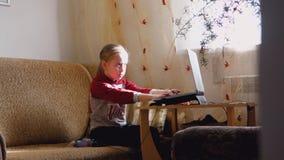 Маленькая девочка наблюдает видео на ноутбуке работы серого цвета девушки компьютера предпосылки сток-видео