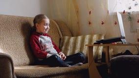 Маленькая девочка наблюдает видео на ноутбуке работы серого цвета девушки компьютера предпосылки видеоматериал