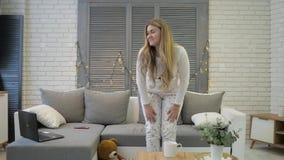 Маленькая девочка сидит на софе и получает вверх от софы С хорошим настроением и красивой улыбкой смотрит вне окно сток-видео