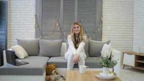 Маленькая девочка сидит на софе и усмехаться акции видеоматериалы