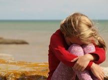 Маленькая девочка сидит сжимающ ее колени и обхватывающ ее голову морем стоковые фотографии rf