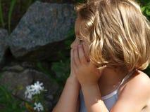 Маленькая девочка смотрит прочь с ее руками над ее ртом стоковая фотография rf
