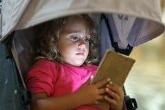 Маленькая девочка смотря сотовый телефон даже когда на каникулах в Paros стоковые изображения rf